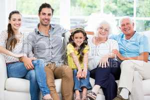 Portrait of smiling family with grandparents on sofa