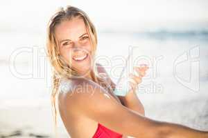 Portrait of happy woman applying sunscreen lotion on the beach
