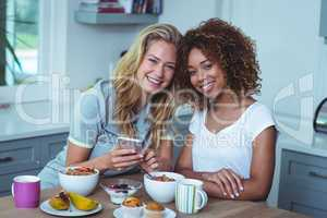 Smiling female friends sitting at breakfast table