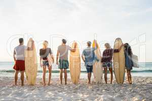 Happy friends standing in line with surfboards