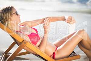 Woman sitting on armchair and applying sunscreen lotion