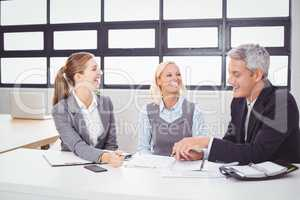 Business people smiling while discussing with client