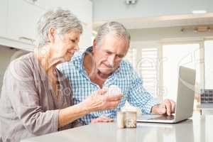 Senior woman showing pills to husband with laptop