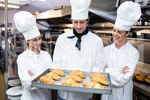 Three chefs holding a tray of baked croissant