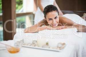 Portrait of young woman receiving massage at health spa