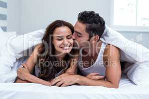 Smiling man kissing woman while lying under blanket