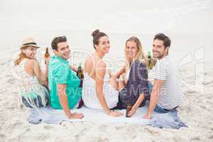 Group of friends sitting side by side on the beach with beer bot