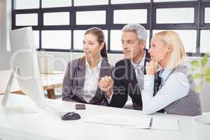 Business professionals working at computer desk