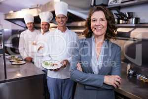 Restaurant manager posing in front of team of chefs