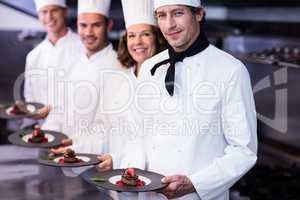 Portrait of happy chefs presenting their dessert plates