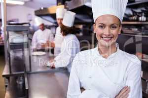 Happy chef standing in commercial kitchen in a restaurant