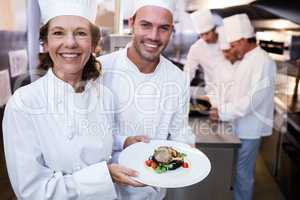 Two chefs presenting their dishes
