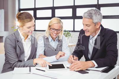 Business people discussing with client over digital tablet
