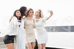 Well dressed women taking a selfie next to a limousine