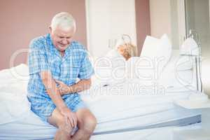 Suffering senior man holding his belly on bed