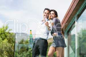 Cheerful couple showing champagne glass at balcony
