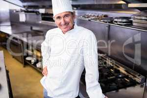 Happy male chef standing in commercial kitchen