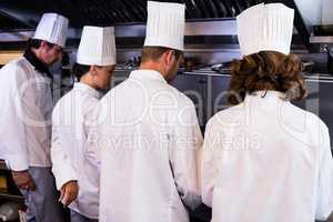Rear view of chefs preparing food in kitchen