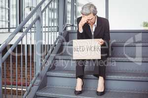 Unemployed businesswoman holding need work placard