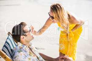 Happy woman applying moisturizer on mans nose