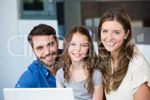 Portrait of smiling family with laptop