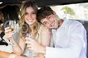 Well dressed couple drinking champagne in a limousine