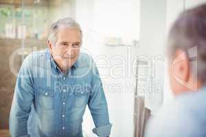 Reflection of smiling senior man on mirror