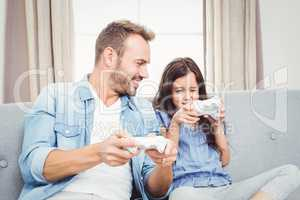 Father playing video game with daughter at home