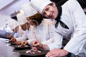 Chefs team finishing dessert plates