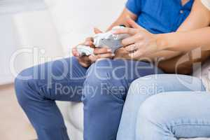 Mid section of couple playing video game