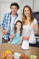 Portrait of smiling family with fruit juice