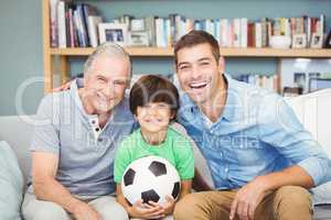 Portrait of happy multi genration family with football