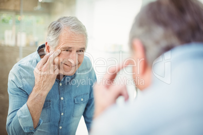 Reflection of senior man looking at skin in mirror
