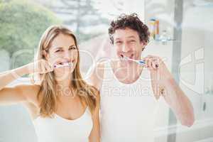 Happy couple brushing teeth