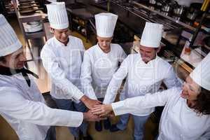 Team of chefs putting hands together