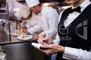 Close-up of waitress with note pad in commercial kitchen