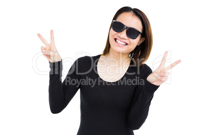 Woman in sunglasses making a v sign