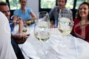 Waiter serving wine to friends in restaurant