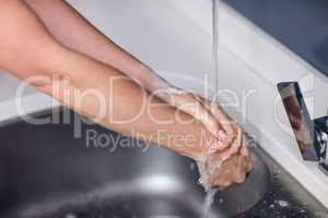 Woman washing hands in washbasin