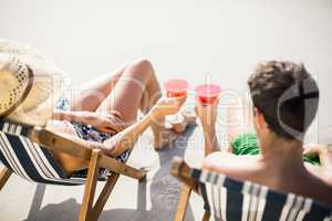 Couple sitting on armchair with cocktail drink