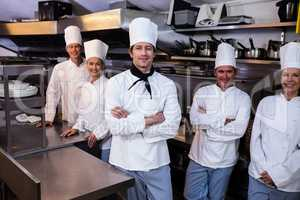 Happy chefs team standing together in commercial kitchen