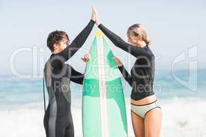 Couple holding a surfboard and giving a high five to each other