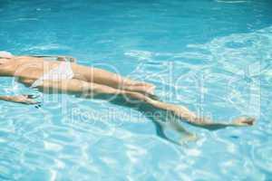 Woman in white bikini floating in swimming pool