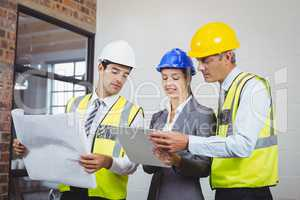Architect team discussing while holding blueprint and clipboard