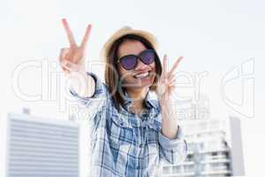 Happy young woman doing a v sign