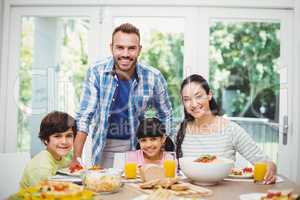 Portrait of cheerful family with father standing at dining table