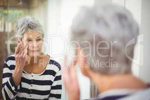 Reflection of senior woman looking at skin in mirror