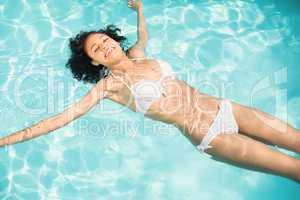 Beautiful woman in white bikini floating in swimming pool