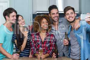 Multi-ethnic friends with alcohol taking selfie in kitchen