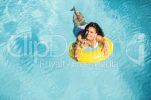 Portrait of woman in white bikini floating on inflatable tube in